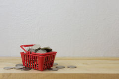 Νομίσματα σε ένα κόκκινο καλαθιών για την έννοια χρημάτων Στοκ Εικόνες