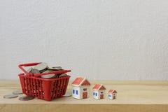 Νομίσματα σε ένα κόκκινο καλαθιών και ένα πρότυπο σπιτιών για την έννοια χρημάτων Στοκ Εικόνες