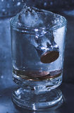 Νομίσματα σε ένα νερό γυαλιού Στοκ Εικόνες