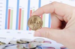 Νομίσματα σε ένα χέρι ενάντια στην επιχείρηση των διαγραμμάτων Στοκ φωτογραφία με δικαίωμα ελεύθερης χρήσης