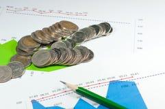 Νομίσματα στο γαλαζοπράσινο υπόβαθρο γραφικών παραστάσεων και διαγραμμάτων με το μολύβι Mo Στοκ Φωτογραφία