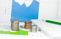 Νομίσματα στο γαλαζοπράσινο υπόβαθρο γραφικών παραστάσεων και διαγραμμάτων με το μολύβι και Στοκ Εικόνα