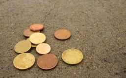 Νομίσματα στο πάτωμα τσιμέντου στοκ εικόνες