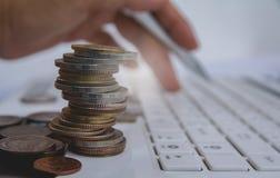 Νομίσματα σωρών στο άσπρο κουμπί Τύπου lap-top και δάχτυλων στο πληκτρολόγιο Στοκ φωτογραφία με δικαίωμα ελεύθερης χρήσης