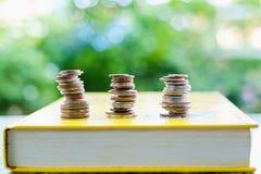 Νομίσματα χρημάτων σε ένα βιβλίο με το θολωμένο φυσικό πράσινο υπόβαθρο στοκ εικόνα με δικαίωμα ελεύθερης χρήσης