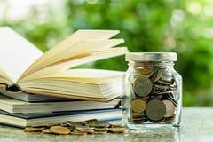 Νομίσματα χρημάτων στο βάζο γυαλιού με το σωρό των ανοιγμένων βιβλίων στοκ φωτογραφία