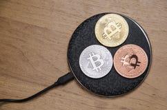 Νομίσματα Bitcoin στην ασύρματη επαναφόρτιση Στοκ Εικόνα