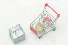 Νομίσματα Bitcoin στο κάρρο και τα δώρα αγορών Άσπρη ανασκόπηση Στοκ Εικόνες