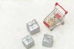 Νομίσματα Bitcoin στο κάρρο και τα δώρα αγορών Άσπρη ανασκόπηση Στοκ φωτογραφίες με δικαίωμα ελεύθερης χρήσης