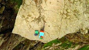 Νορβηγία κορίτσι στην άκρη του βράχου Trolltunga Εναέριο vie απόθεμα βίντεο