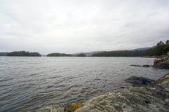 Νορβηγικά φιορδ και βουνά Δύσκολα ακτή, κύματα και δέντρα Στοκ Εικόνα