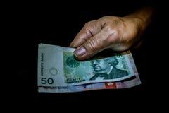 Νορβηγικοί λογαριασμοί κορωνών στο χέρι ενός προσώπου που απομονώνεται στο Μαύρο στοκ εικόνα