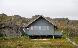 Νορβηγικό ξύλινο σπίτι στα ξυλοπόδαρα κάτω από τον απότομο βράχο Στοκ φωτογραφία με δικαίωμα ελεύθερης χρήσης