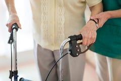 Νοσηλευτικός βοηθός που βοηθά την ανώτερη γυναίκα με το πλαίσιο περπατήματος στοκ εικόνες