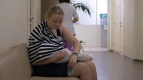 Νοσηλευτικό μωρό το γυναικών κατά αναμονή του γιατρού στο κέντρο υγείας απόθεμα βίντεο
