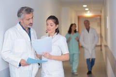 Νοσηλευτικό προσωπικό που εξετάζει τη γραφική εργασία στο διάδρομο νοσοκομείων στοκ εικόνες με δικαίωμα ελεύθερης χρήσης