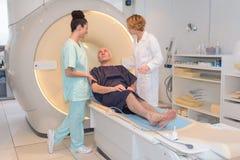 Νοσηλευτικό προσωπικό που μιλά στον ασθενή στον CT-ανιχνευτή στοκ εικόνα