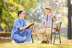 Νοσοκόμα και ένας ηλικιωμένος έχοντας τη συνομιλία στο πάρκο Στοκ Εικόνες