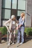 νοσοκόμα και ανώτερος ασθενής με τον περιπατητή που χαμογελά ο ένας τον άλλον περιποίηση εξωτερικού στοκ φωτογραφία με δικαίωμα ελεύθερης χρήσης
