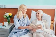 νοσοκόμα και ανώτερο βιβλίο ανάγνωσης γυναικών και χαμόγελο του ενός τον άλλον στην περιποίηση στοκ φωτογραφίες