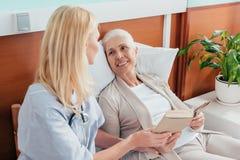 νοσοκόμα και ανώτερο υπομονετικό βιβλίο ανάγνωσης και χαμόγελο του ενός τον άλλον στην περιποίηση στοκ φωτογραφία με δικαίωμα ελεύθερης χρήσης