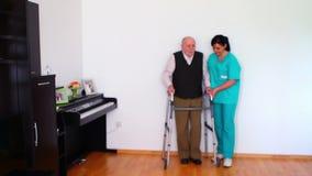 Νοσοκόμα και ηλικιωμένο ανώτερο άτομο που χρησιμοποιούν το πλαίσιο περπατήματος απόθεμα βίντεο
