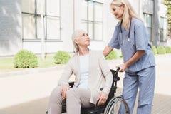 νοσοκόμα και χαμογελώντας ανώτερος ασθενής στην αναπηρική καρέκλα που χαμογελούν ο ένας τον άλλον περιποίηση εξωτερικού στοκ φωτογραφία με δικαίωμα ελεύθερης χρήσης