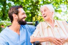 Νοσοκόμα που έχει τη συνομιλία με την ανώτερη γυναίκα στη ιδιωτική κλινική στοκ εικόνα