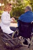 Νοσοκόμα που δίνει την ιατρική στο ανώτερο άτομο στην αναπηρική καρέκλα υπαίθρια στοκ φωτογραφίες