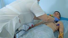 Νοσοκόμα που αφαιρεί τα μαξιλάρια ECG από τον αρσενικό ασθενή Στοκ Εικόνα