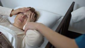 Νοσοκόμα που βάζει τη συμπίεση στο θηλυκό μέτωπο ασθενών στο νοσοκομείο, υγειονομική περίθαλψη απόθεμα βίντεο
