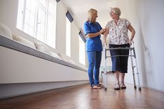 Νοσοκόμα που βοηθά την ανώτερη χρήση γυναικών ένα πλαίσιο περπατήματος, πλήρες μήκος στοκ εικόνα με δικαίωμα ελεύθερης χρήσης