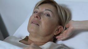 Νοσοκόμα που βοηθά τη ηλικιωμένη γυναίκα για να βάλει στο νοσοκομειακό κρεβάτι, κυρία που αισθάνεται αδύνατο μετά από τη χειρουργ απόθεμα βίντεο