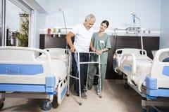Νοσοκόμα που βοηθά τον ανώτερο ασθενή σε χρησιμοποίηση του περιπατητή στο κέντρο Rehab Στοκ Φωτογραφία