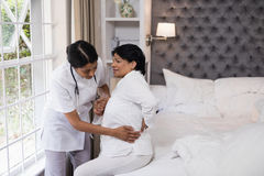 Νοσοκόμα που βοηθά το θηλυκό υπομονετικό βάσανο με τον πόνο στην πλάτη στο κρεβάτι Στοκ Εικόνες