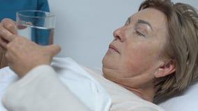 Νοσοκόμα που δίνει τα χάπια στο θηλυκό ασθενή που βρίσκεται στο κρεβάτι, αθεράπευτη ασθένεια, υγειονομική περίθαλψη απόθεμα βίντεο