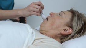 Νοσοκόμα που δίνει το σιρόπι στον παλαιό θηλυκό ασθενή που βρίσκεται στο κρεβάτι, υγειονομική περίθαλψη απόθεμα βίντεο