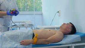 Νοσοκόμα που εκτελεί electrocardiography σε έναν αρσενικό ασθενή φιλμ μικρού μήκους