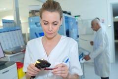 Νοσοκόμα που ελέγχει τα επίπεδα αποθεμάτων στο φαρμακείο νοσοκομείων που χρησιμοποιεί τον ανιχνευτή στοκ εικόνες