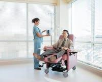Νοσοκόμα που ενεργοποιεί IV μηχανή για τον ασθενή κατά τη διάρκεια Στοκ Εικόνες