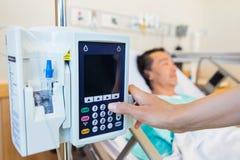Νοσοκόμα που ενεργοποιεί IV μηχανή ενώ ασθενής που βρίσκεται επάνω Στοκ Εικόνες