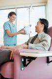 Νοσοκόμα που εξετάζει τον ασθενή λειτουργούσα IV Στοκ εικόνες με δικαίωμα ελεύθερης χρήσης