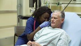 Νοσοκόμα που εξετάζει τον ώριμο αρσενικό ασθενή στο νοσοκομειακό κρεβάτι απόθεμα βίντεο
