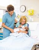 Νοσοκόμα που εξετάζει το υπομονετικό γάλα σίτισης στο μωρό Στοκ εικόνες με δικαίωμα ελεύθερης χρήσης