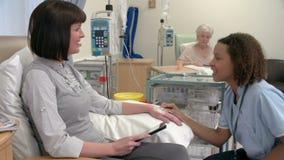 Νοσοκόμα που ελέγχει στο θηλυκό ασθενή που έχει τη χημειοθεραπεία απόθεμα βίντεο