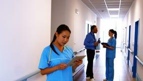Νοσοκόμα που κρατά την ψηφιακή ταμπλέτα στο νοσοκομείο απόθεμα βίντεο