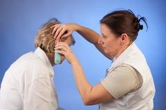 Νοσοκόμα που μετρά τη θερμοκρασία στην ανώτερη γυναίκα Στοκ Εικόνες