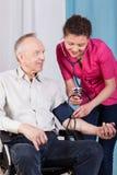 Νοσοκόμα που μετρά τη πίεση του αίματος των ατόμων με ειδικές ανάγκες Στοκ Εικόνες