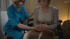 Νοσοκόμα που μιλά εγκάρδια στη ηλικιωμένη γυναίκα στην αναπηρική καρέκλα που υποστηρίζει την, ηλικιωμένο σπίτι φιλμ μικρού μήκους