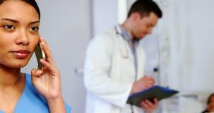 Νοσοκόμα που μιλά στο κινητό τηλέφωνο απόθεμα βίντεο